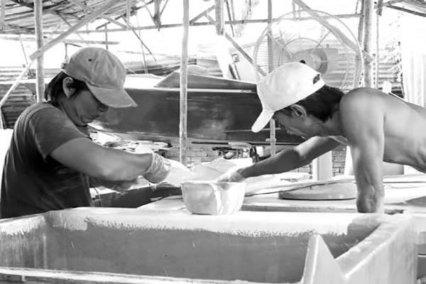 Cha con ông Bình SVC trong xưởng chế tác sản phẩm du lịch sông nước. Ảnh: Hoàng Yến