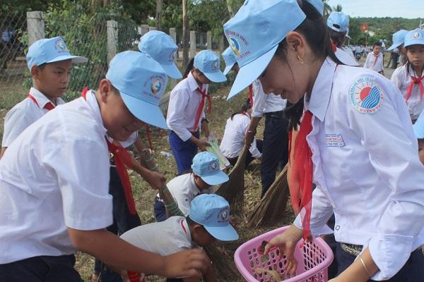 Học sinh Trường THCS Huỳnh Thúc Kháng dọn vệ sinh khuôn viên trường để hưởng ứng Tuần lễ quốc gia nước sạch và vệ sinh môi trường - Ảnh: M.DUYÊN
