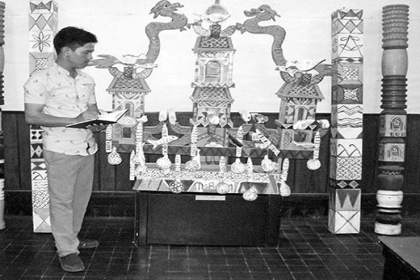 Tác giả, bên mô hình thuyền Ka go, trưng bày tại Bảo tàng tỉnh Khánh Hòa. Ảnh: Mai Thi
