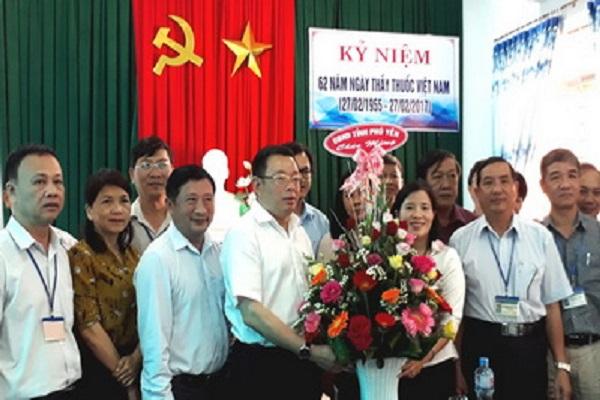 Đồng chí Hoàng Văn Trà tặng hoa chúc mừng Sở Y tế - Ảnh: YÊN LAN