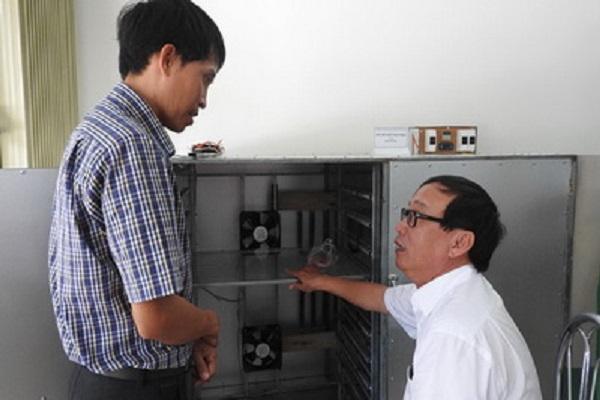 Anh Đặng Xuân Thanh (trái) giới thiệu máy sấy khô thực phẩm - Ảnh: THÁI HÀ