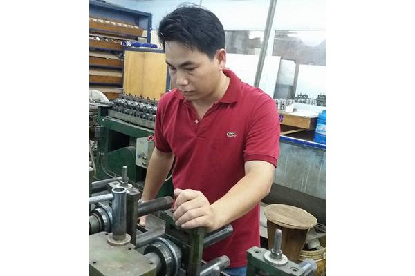 Anh Nguyễn Văn Tháp đang điều khiển máy dập kim loại - Ảnh: NGỌC HÂN