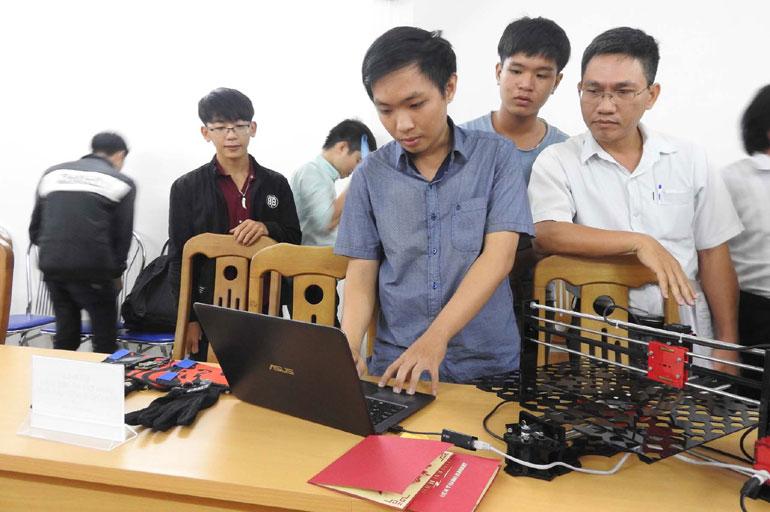 Ngô Huỳnh Ngọc Khánh (bên máy tính) giới thiệu giải pháp Máy cắt laser công nghệ IoT đến ban giám khảo - Ảnh: THÁI HÀ