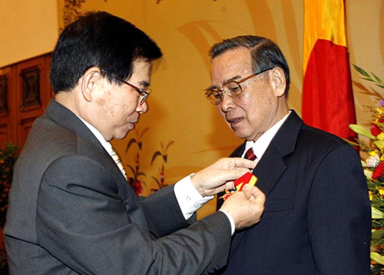 Chủ tịch nước Nguyễn Minh Triết gắn Huân chương Sao Vàng cho nguyên Thủ tướng Phan Văn Khải tại Văn phòng Chính phủ ngày 5/1/2008 - Ảnh: TTXVN