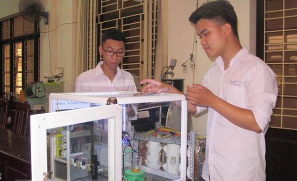 Em Giang Quốc Hoàn và Đỗ Hữu Toàn kiểm tra mô hình robot thí nghiệm hóa học - Ảnh: TTXVN