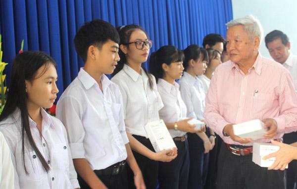 Ông Lê Văn Hữu, Chủ tịch Hội Khuyến học tỉnh Phú Yên trao máy tính bảng cho học sinh nghèo hiếu học - Ảnh: KIM LIÊN