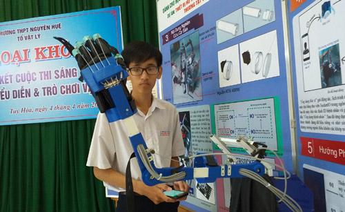 """Huỳnh Đức Nhâm giới thiệu sản phẩm """"Thiết bị hỗ trợ thực hiện phác đồ điều trị thương tật tay tại nhà"""" - Ảnh: THÁI HÀ"""