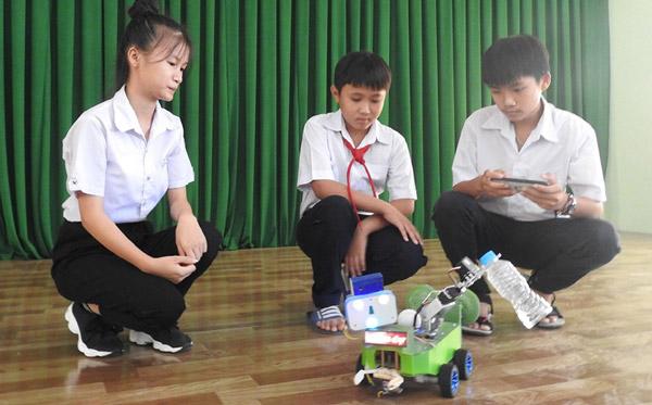 Trần Thị Mỹ Thoai (trái) và Bùi Thành Công (phải), học sinh lớp 9 Trường tiểu học và THCS Lê Quý Đôn (TX Sông Cầu) giới thiệu sản phẩm Smart Family Robot - Ảnh: THÁI HÀ