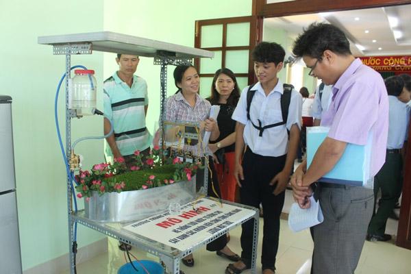 Đặng Huỳnh Nhật Khánh (thứ hai, bên phải sang) thuyết minh mô hình với thành viên giám khảo