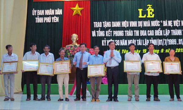 Các đồng chí Huỳnh Tấn Việt và Trần Hữu Thế trao quyết định truy tặng Danh hiệu vinh dự nhà nước Bà mẹ VNAH cho các thân nhân - Ảnh: THÙY THẢO