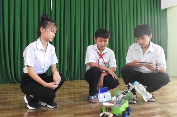 Hai em Trần Thị Mỹ Thoai (bên trái) và Bùi Thành Công (bên phải) - TX Sông Cầu, giới thiệu sản phẩm Smart family robot đạt giải nhì tại cuộc thi Sáng tạo thanh thiếu niên và nhi đồng lần 4 (năm 2019). Ảnh