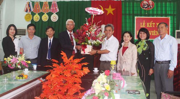 Đồng chí Lương Minh Sơn và lãnh đạo Sở GD-ĐT tặng hoa, chúc mừng thầy cô Trường THPT Nguyễn Huệ. Ảnh: TRUNG HIẾU