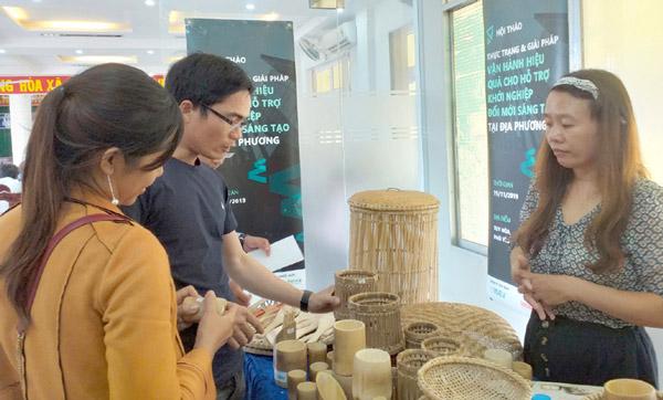 Chị Lê Thị Trâm (bên phải) giới thiệu sản phẩm xanh, thân thiện với môi trường do doanh nghiệp mình sản xuất đến khách hàng. Ảnh: THÁI HÀ