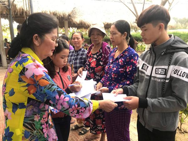 Bà Huỳnh Thị Kim Hương, đại diện Hội Đồng hương Phú Yên tại TP Hồ Chí Minh trao quà Tết cho người dân xã An Chấn - Ảnh: MINH DƯƠNG