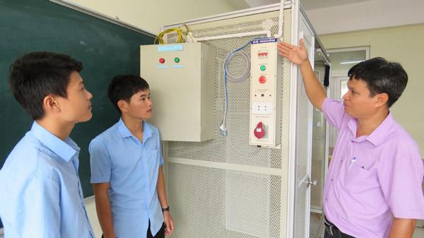 Thầy Nguyễn Thanh Tước hướng dẫn sinh viên ngành Ðiện học tập thông qua mô hình do thầy tự làm - Ảnh: MẠNH THÚY