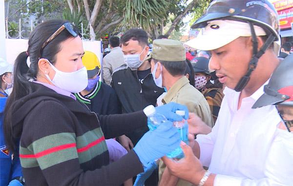 Lực lượng đoàn viên của hai đơn vị phát chai dung dịch rửa tay cho người dân. Ảnh: NHƯ THANH