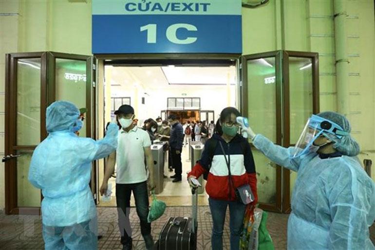 Hành khách được đo thân nhiệt trước khi vào ga Hà Nội - Ảnh: TTXVN