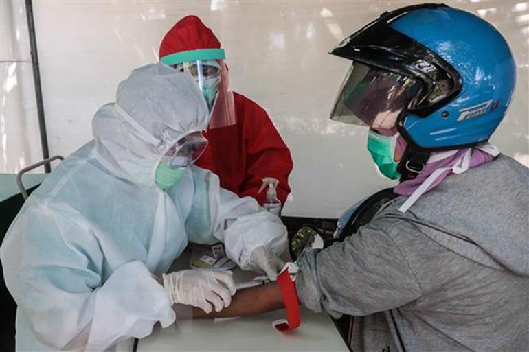 Nhân viên y tế xét nghiệm nhanh COVID-19 cho người dân tại Surabaya, Indonesia, ngày 22/4/2020 - Nguồn: THX/TTXVN