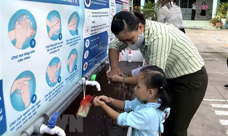 Giáo viên hướng dẫn trẻ rửa tay trước khi vào lớp để phòng dịch COVID-19. Ảnh: TTXVN