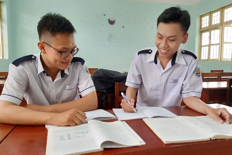Nguyễn Thanh Phúc (phải) trao đổi bài tập với bạn học cùng lớp. Ảnh: NGUYỄN CHƯƠNG