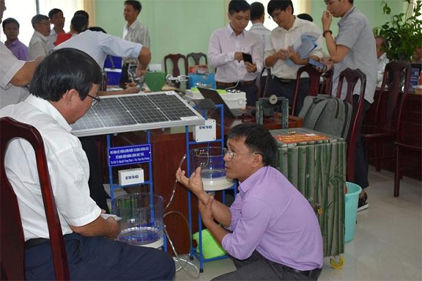 Tác giả Phạm Duy Phượng (phải) giới thiệu mô hình hệ thống bơm nước tự động không dây, sử dụng điện năng lượng mặt trời. Ảnh: HOÀNG HÀ THẾ