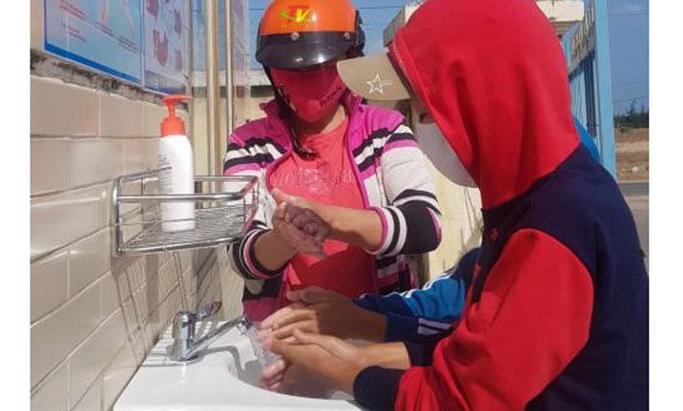 Người dân rửa tay trước khi vào một cơ sở y tế. Ảnh: YÊN LAN