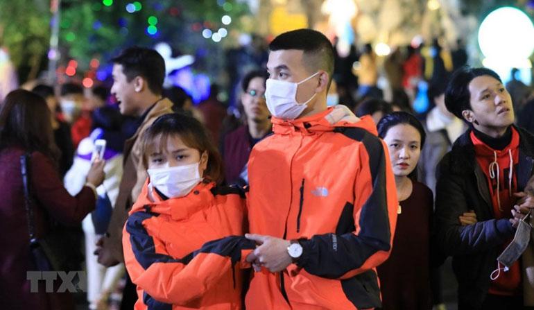 Chỉ một số ít người dân chấp hành đeo khẩu trang phòng, chống dịch đi đón Giáng sinh. Ảnh: TTXVN