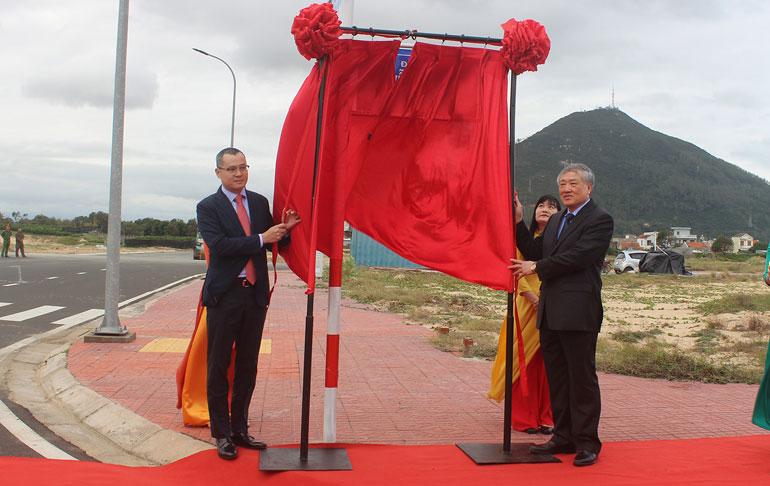 Đồng chí Nguyễn Hòa Bình (phải) và đồng chí Phạm Đại Dương thực hiện nghi thức kéo băng gắn biển tên đường Nguyễn Kim Vang. Ảnh:NHƯ THANH