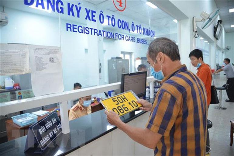 Cấp, đổi biển số nền màu vàng cho người dân - Ảnh: TTXVN