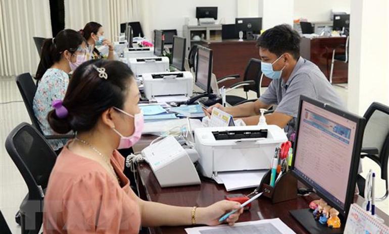 Cán bộ công chức Trung tâm Phục vụ hành chính công tỉnh Ninh Thuận giải quyết hồ sơ, thủ tục hành chính cho các doanh nghiệp. Ảnh: TTXVN