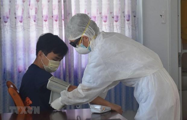 Nhân viên y tế kiểm tra sức khỏe cho người được cách ly phòng bệnh COVID-19. (Ảnh: Hoàng Nhị/TTXVN)