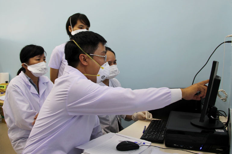 Cán bộ y tế đang phân tích các mẫu xét nghiệm COVID-19. Ảnh: NGỌC NHƯ