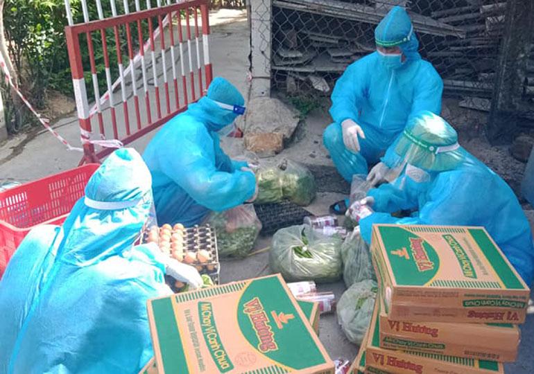 Mặt trận xã Bình Kiến cùng các thành viên tổ phòng chống COVID-19 cộng đồng, tiếp nhận các mặt hàng nhu yếu phẩm để phân bổ cho người dân. Ảnh: LÊ THỊ THU